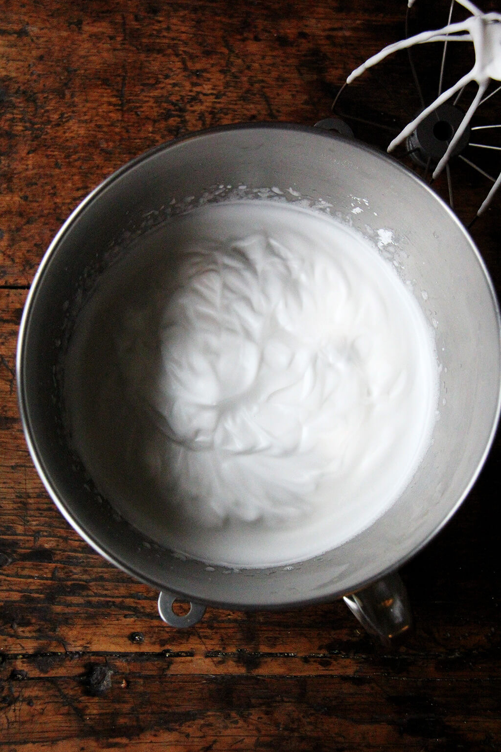 The bowl of a stand mixer filled with whipped aquafaba.