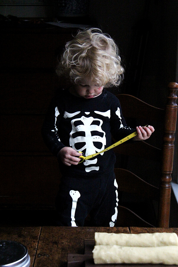 Child dressed in skeleton pjs holding a tape measure.
