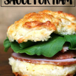 A biscuit sandwich of ham, arugula, and mustard sauce.