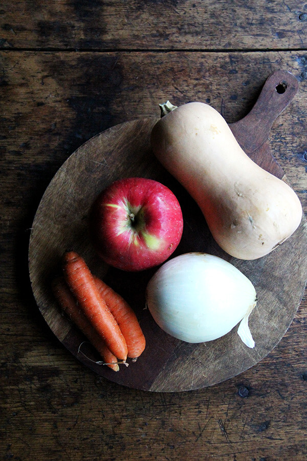 A board of ingredients: apple, onion, carrots, and butternut squash.