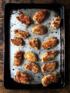 A sheet pan of baked chicken fingers.