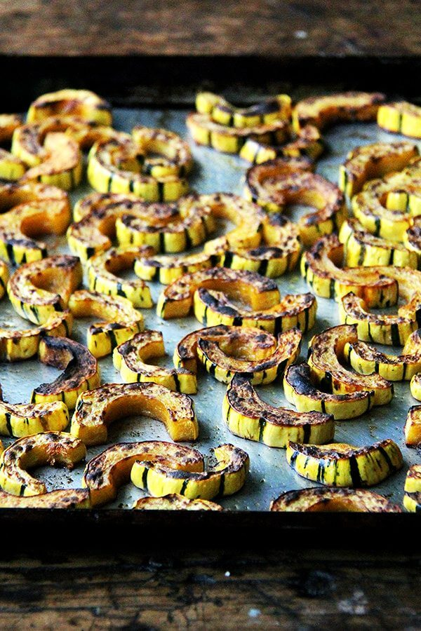 A sheet pan with roasted-broiled delicata squash.
