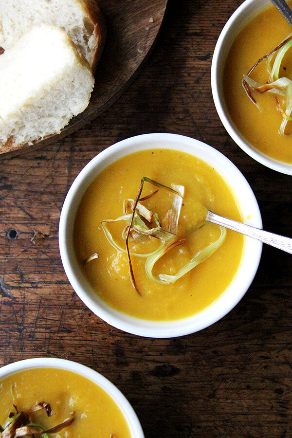 Bowls of butternut squash and apple soup topped with crispy leeks.