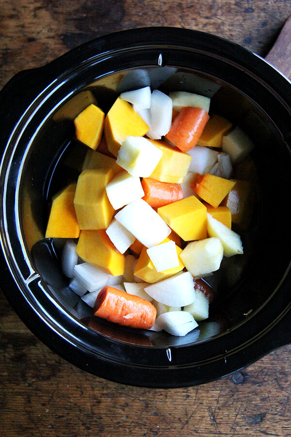 All of the vegetables for the soup in a slow cooker.