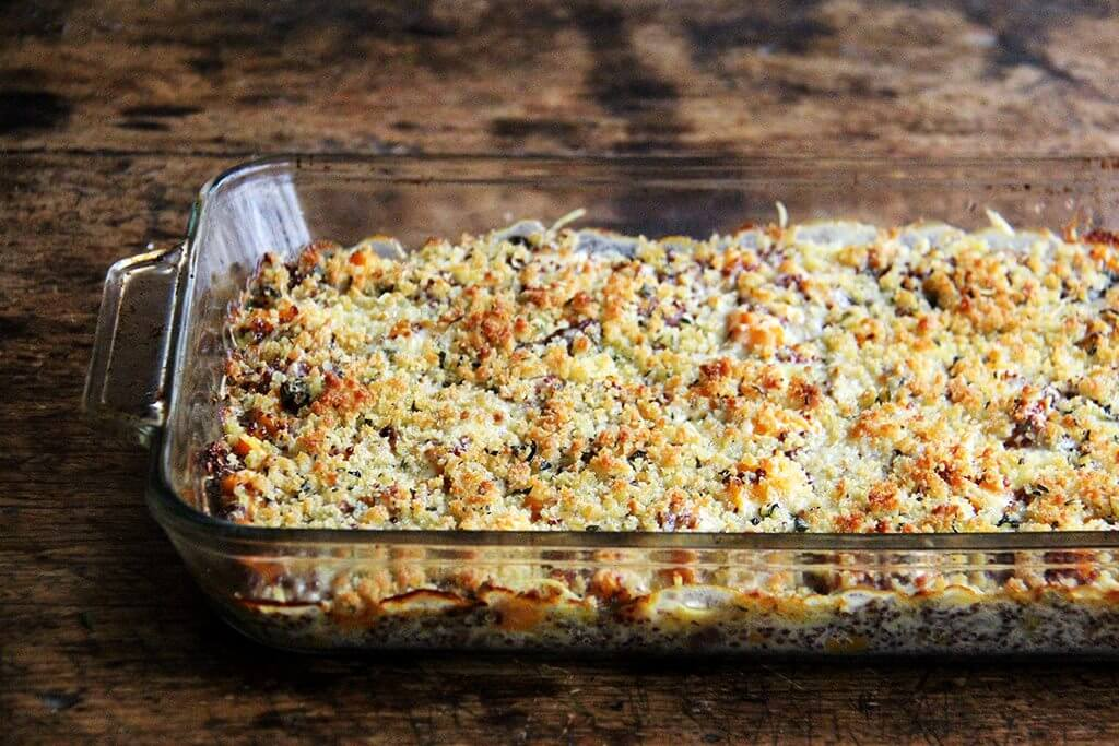 A 9x13-inch pan filled with a just-baked quinoa bake with roasted butternut squash and onions.
