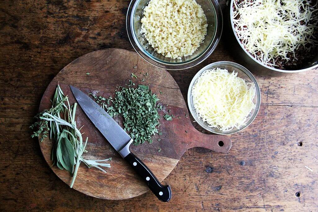 A board of chopped herbs aside bowls of bread crumbs, cheese, and quinoa.