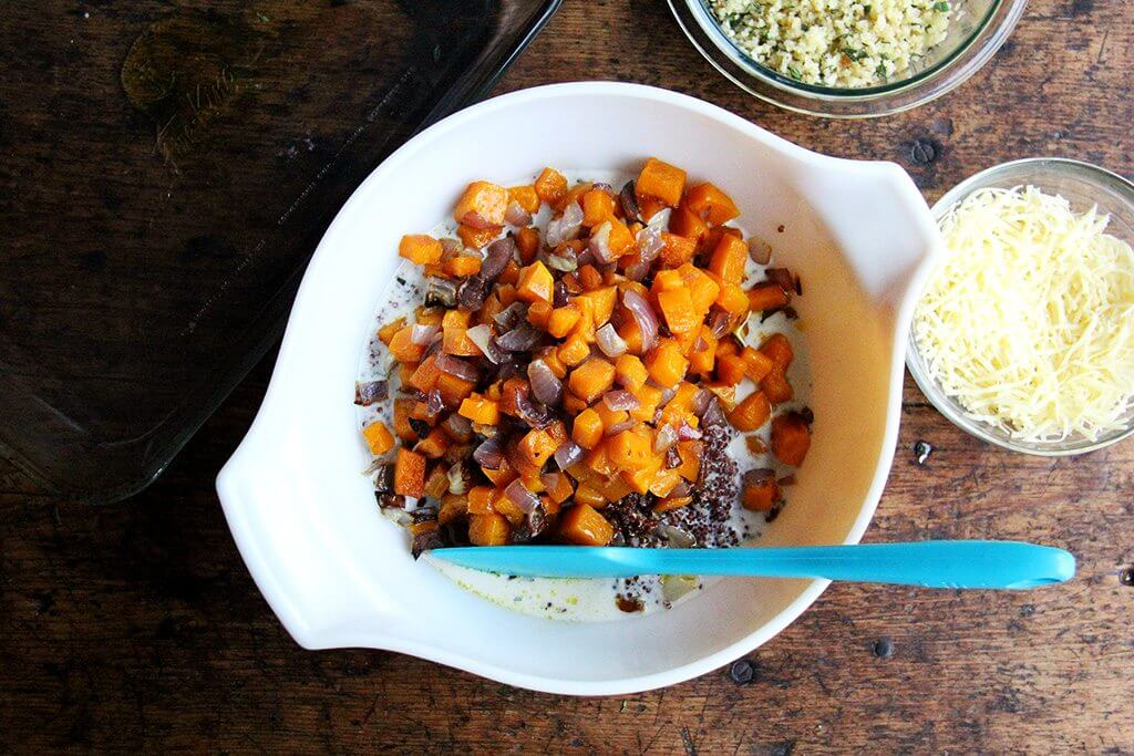 A bowl of roasted squash and onions, quinoa, and milk.
