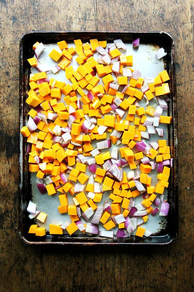 A sheet pan of cubed squash and onion ready to be roasted.