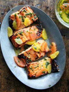 A sizzle platter holding broiled arctic char dressed in a citrus sauce.
