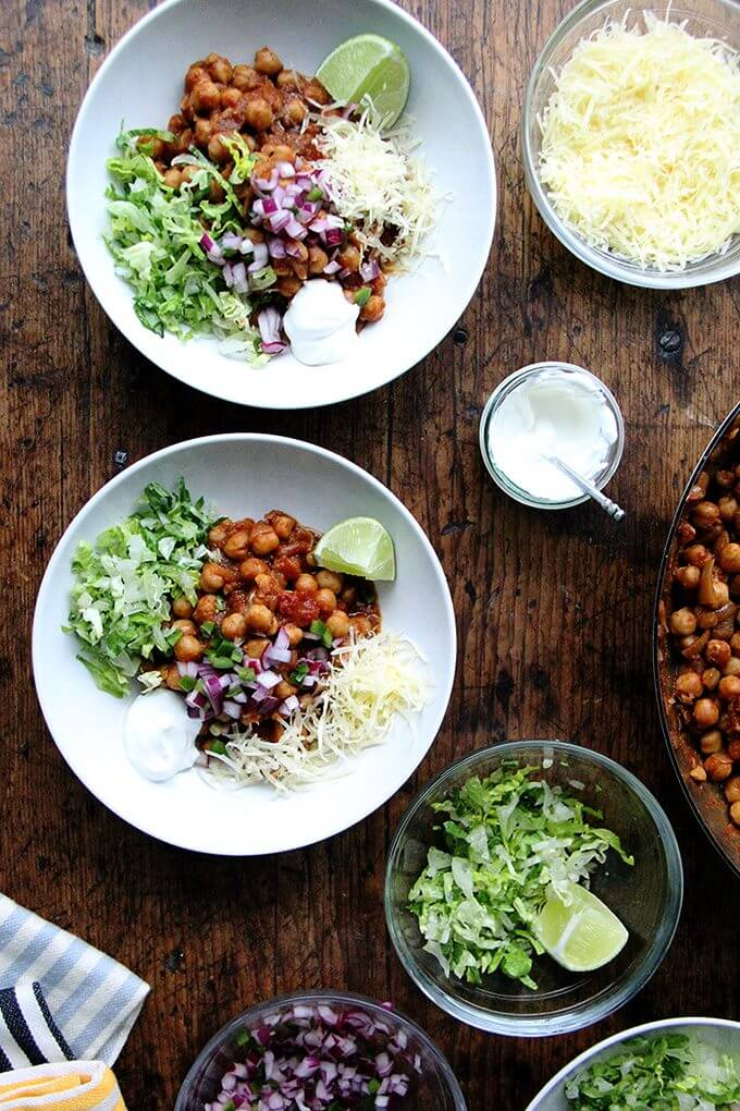 Assembled chickpea taco bowls with lettuce, lime, sour cream, and cheese.