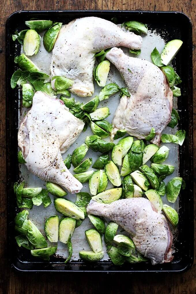 A sheet pan with uncooked chicken legs and Brussels sprouts.