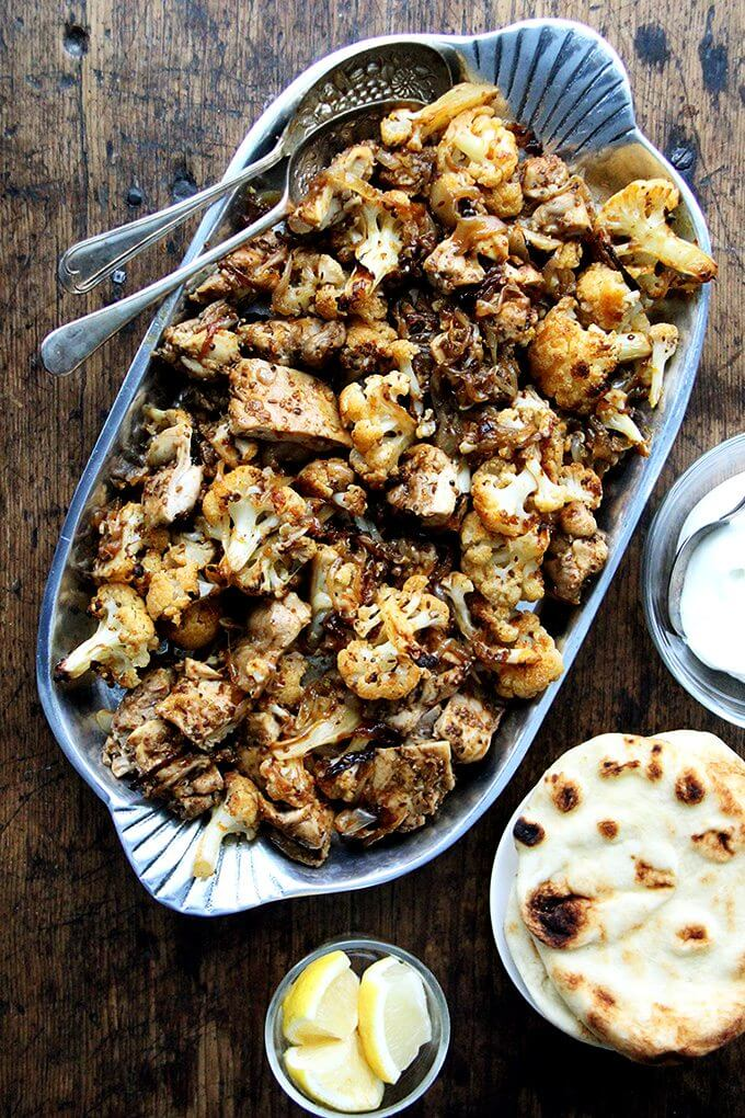 """Heres the gist of this sheet pan chicken and cauliflower """"shawarma"""": cauliflower florets, a sliced onion, and a few unpeeled  garlic cloves dressed with olive oil and a few thyme sprigs roast for 40 minutes on a sheet pan, where they caramelize before they meet a showering of salty, grated parmesan. The combination of sweet and salty, as you can imagine, is incredibly delicious. // alexandracooks.com"""