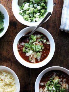 A bowl of weeknight chili topped with scallions and cheddar.