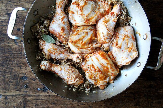 An overhead shot of a sauté pan with onion, ras-el-hanout, rice, and chicken.
