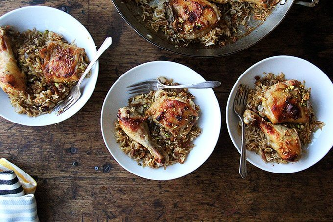 Overhead shot of three bowls of Moroccan chicken and rice with forks.