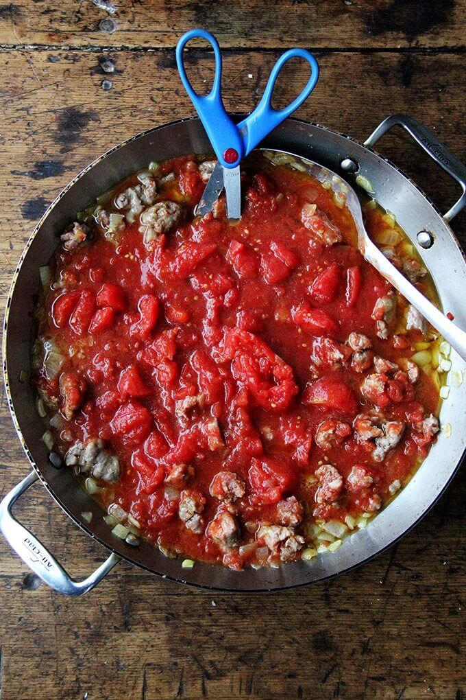 Cutting the tomatoes with scissors in a sauté pan filled with sausage, onions and tomatoes.