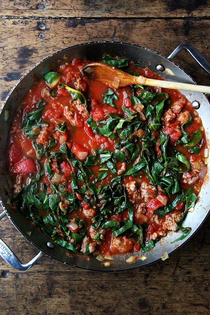 A sauté pan filled with a pan of tomato sauce made with sausage and Swiss chard.