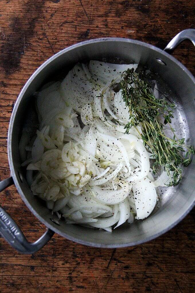A large pot filled with onions, garlic, salt, pepper, and thyme.
