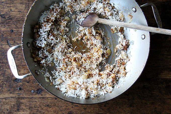 An overhead shot of a sauté pan with onion, ras-el-hanout, and rice.