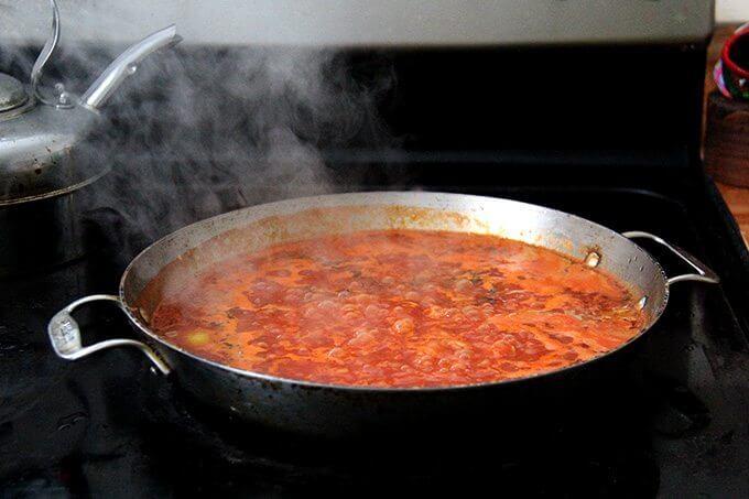 Farro risotto simmering stovetop in a sauté pan.