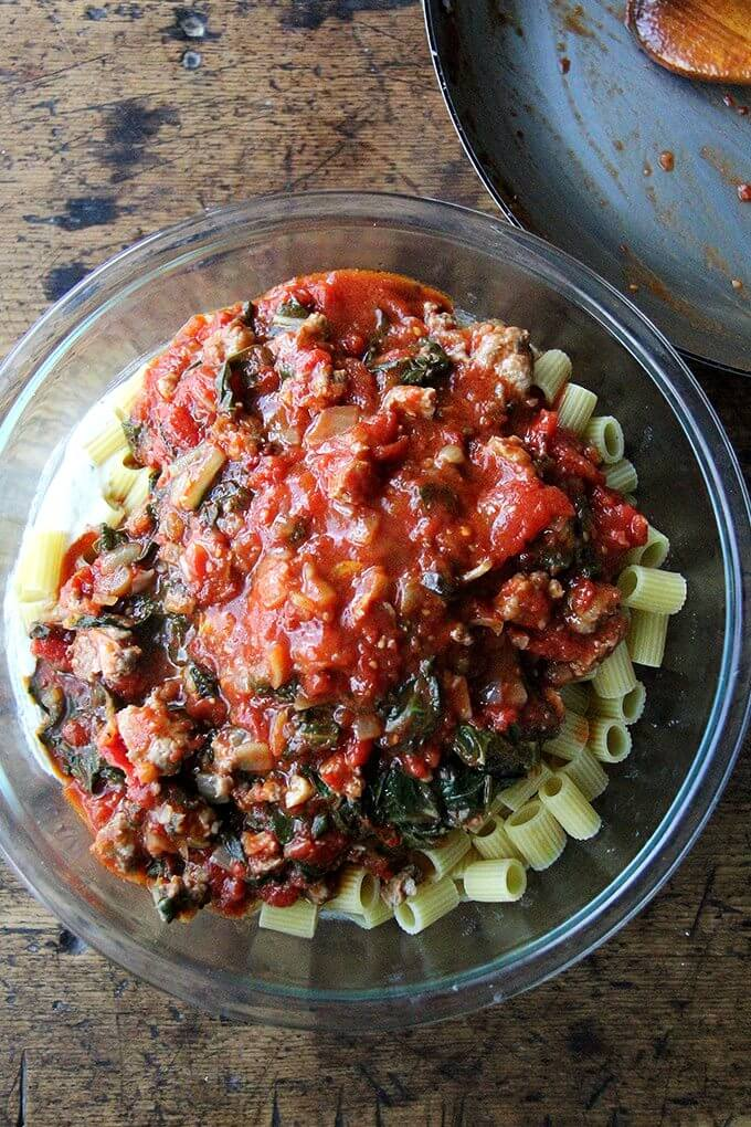 A bowl of pasta tossed with sausage tomato sauce.