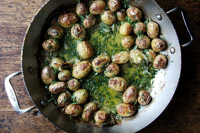 A braiser filled with roasted potatoes and tarragon.