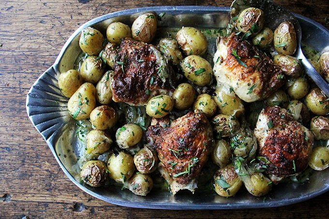 A platter filled with one-pan roast chicken and potatoes with tarragon.