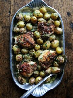 A platter filled with one-pan roasted chicken thighs and potatoes.