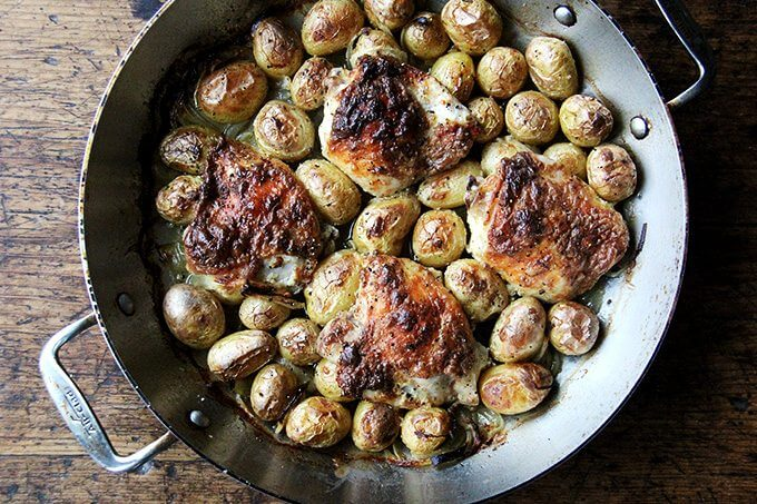 Just-cooked chicken and potatoes in braiser.