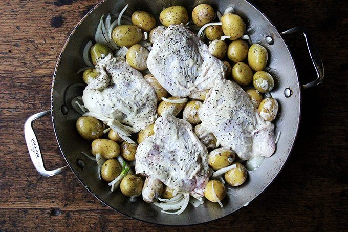 A braiser filled with potatoes, onions, chicken thighs, salt and pepper.