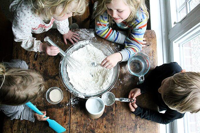 Overhead shot of children whisking together the pizza dough.