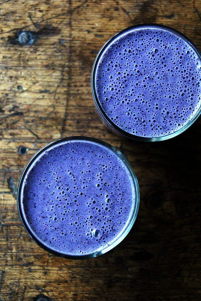 An overhead shot of two  blueberry-almond smoothies.