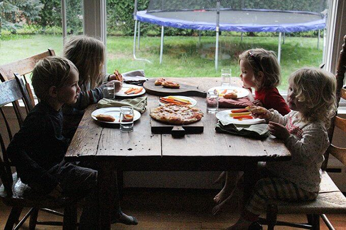 Sideview of 4 kids eating skillet pizza and carrots.