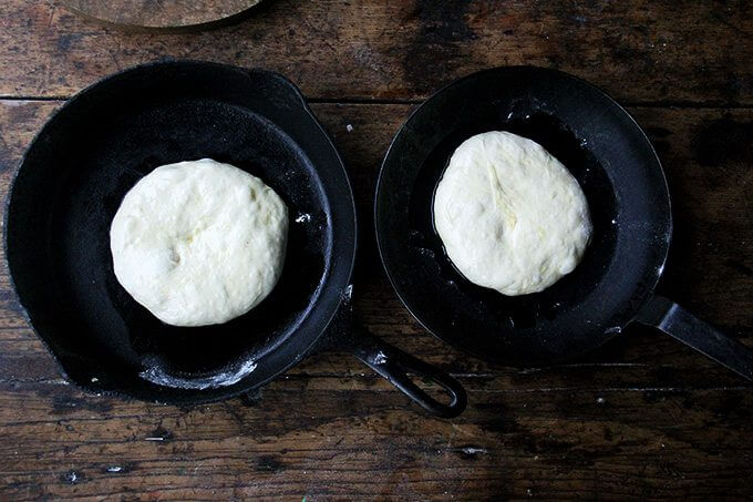 Two cast iron skillets holding pizza dough.
