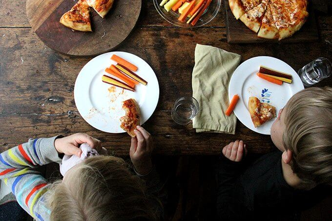 Overhead shot of kids eating skillet pizza and carrots.
