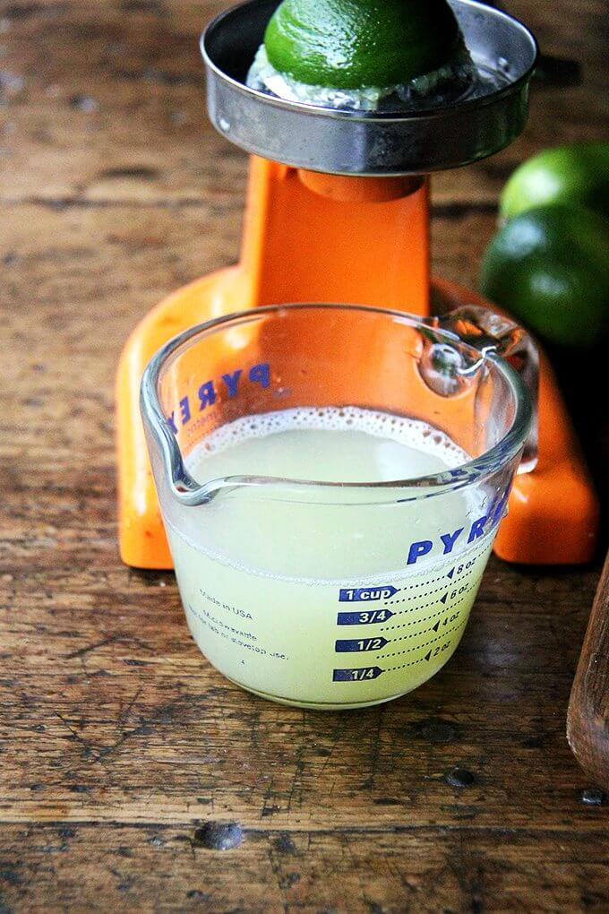 A cup of fresh-squeezed lime juice in a liquid measure.