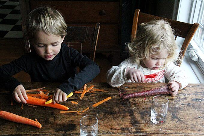 Two kids peel carrots.