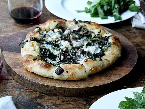 A kale and mushroom skillet pizza on a board.