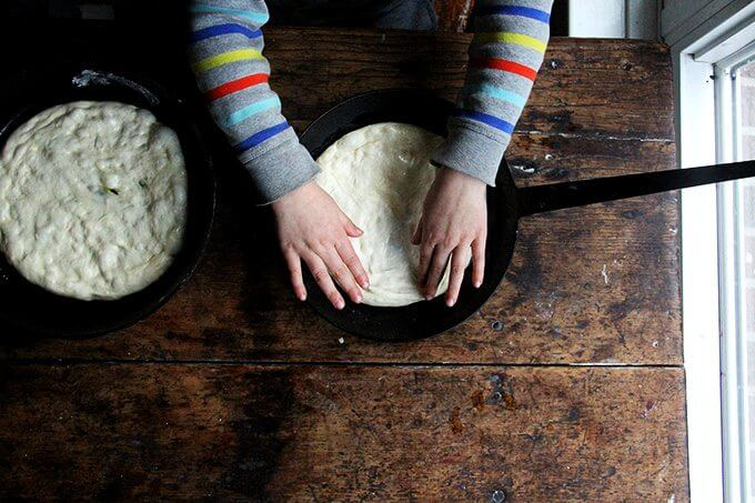 A child spreads pizza dough in a skillet.