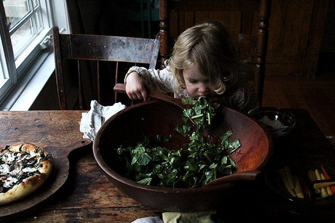 Toddler eating kale salad straight from the bowl.