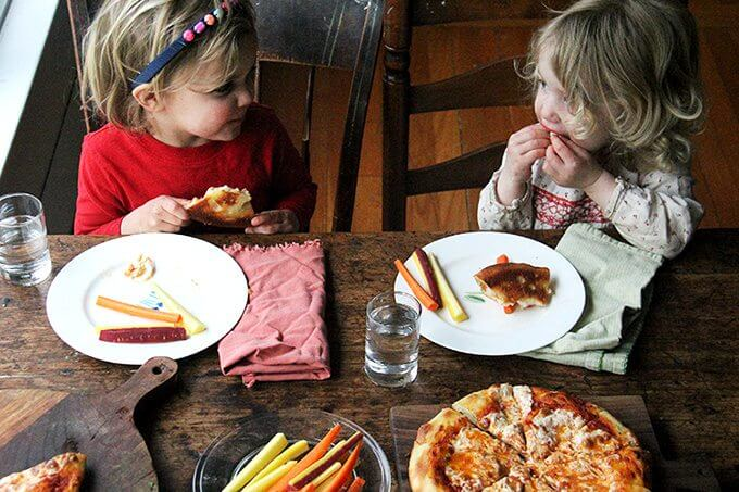 Two toddlers sitting at a table eating pizza.