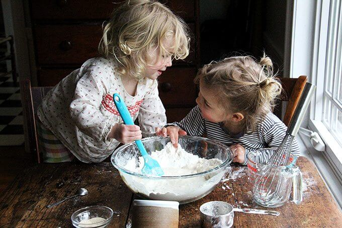 Sideview of two kids making pizza dough.
