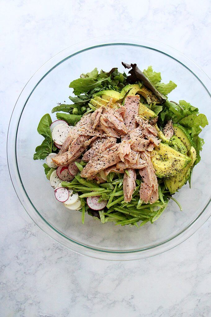 A large bowl filled with a salad of greens, radishes, avocado, jarred tuna and a shallot vinaigrette.