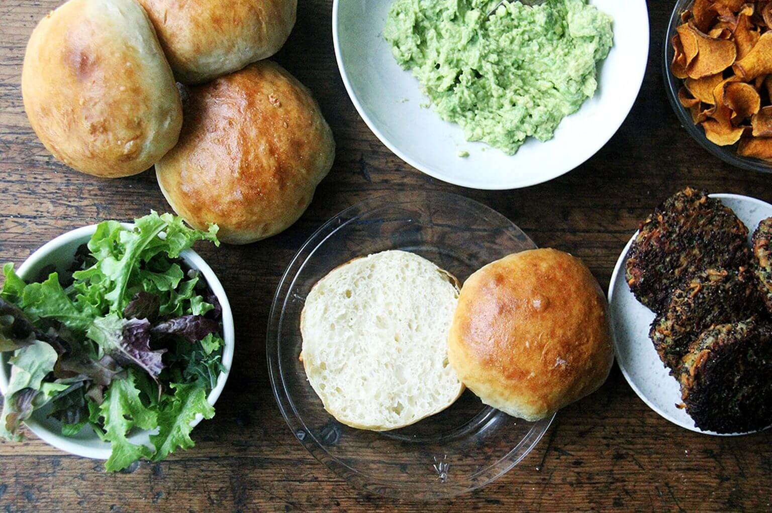 A board filled with homemade brioche buns, mashed avocado, and mushroom-quinoa burger patties.