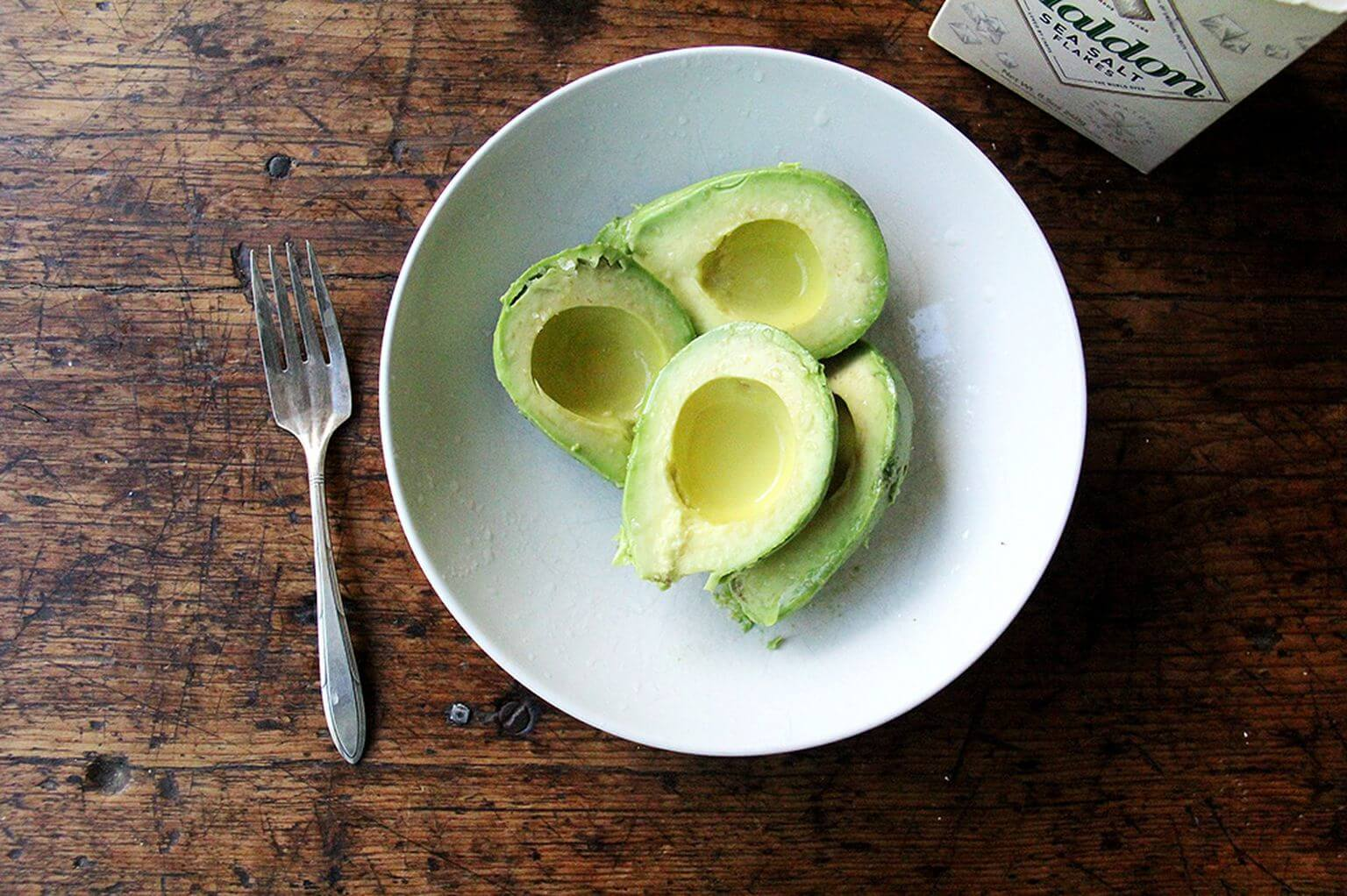 A bowl of two avocados.