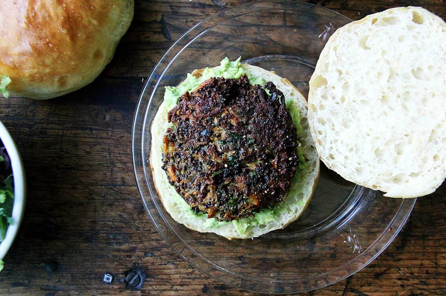Overhead shot of open-face veggie burger on a brioche bun with mashed avocado.
