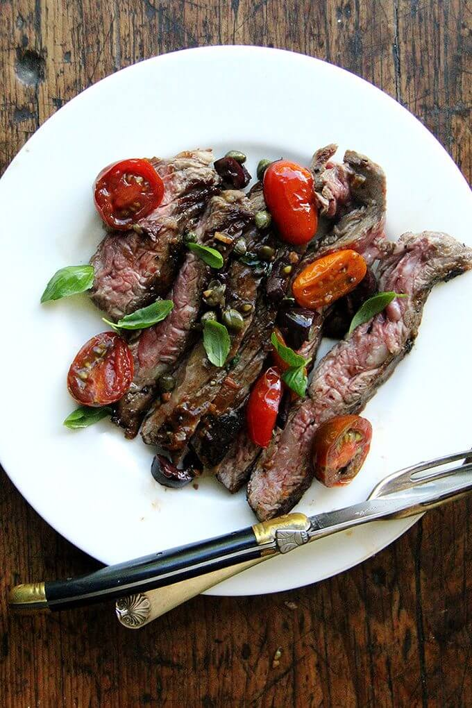 In this skirt steak nicoise, while the skirt steak rests, you'll make a simple sauce Niçoise. After halving cherry tomatoes, coarsely chopping olives, and tossing the two with capers, you'll briefly sauté the mix with olive oil and garlic. After just a few minutes, the tomatoes will begin to break down, releasing juices and sweetening as they soften. A squeeze of fresh lemon juice at the end offers a welcomed hit of acidity. // alexandracooks.com