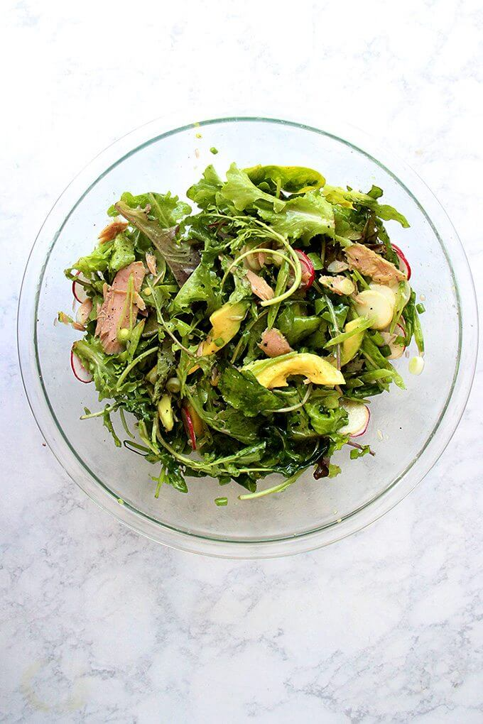 A large bowl filled with a salad of greens, radishes, avocado, jarred tuna and a shallot vinaigrette all tossed together.