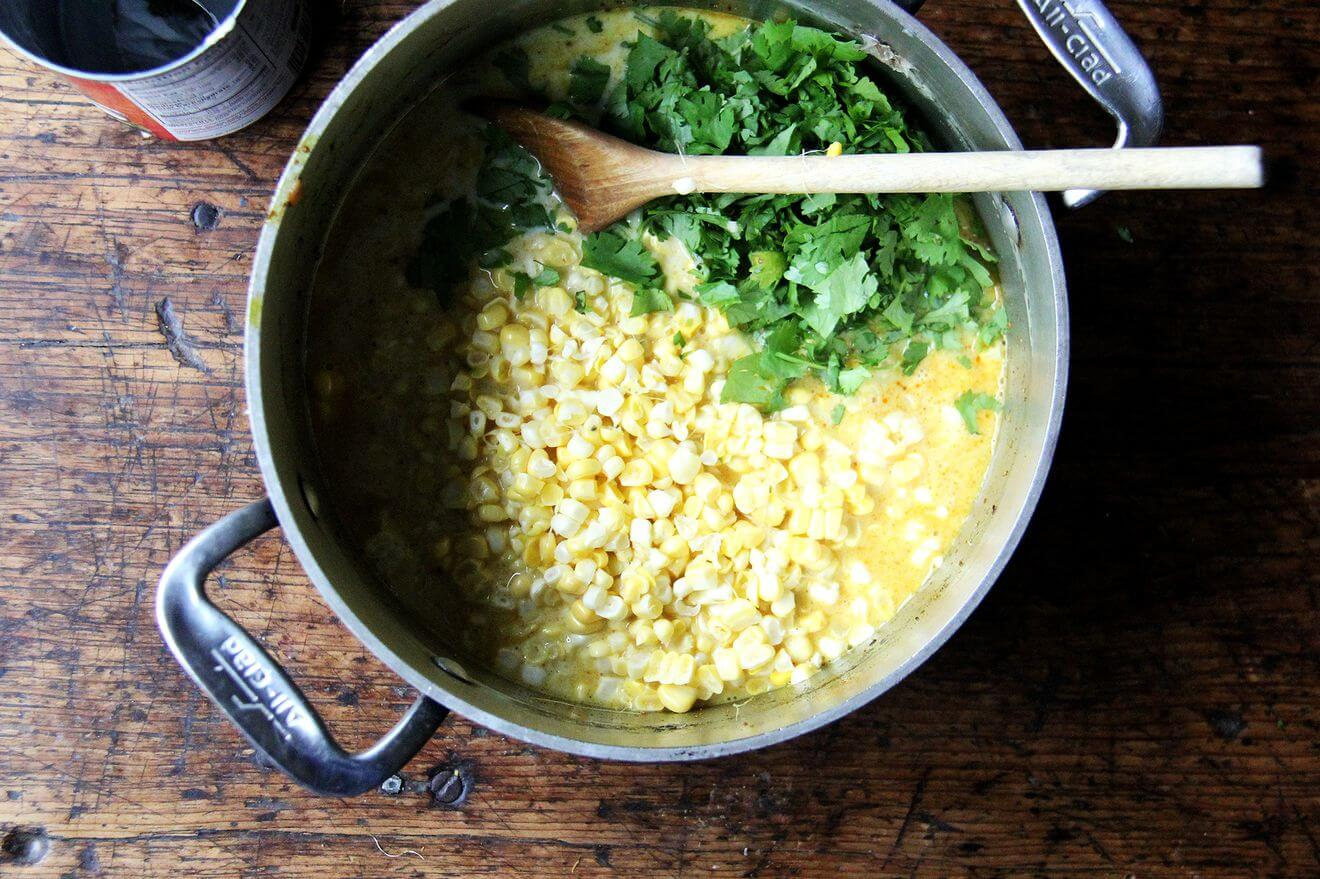 A pot filled with curried corn soup and cilantro.