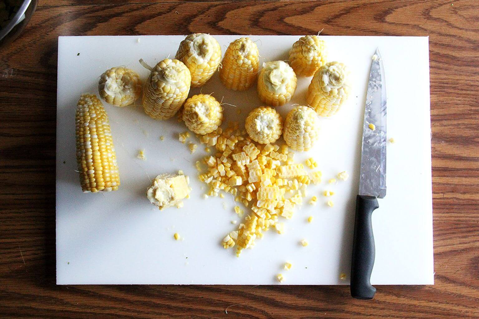 A cutting board with corn and stripped kernels and a knife.